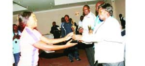 •INSPECTOR General of Police, Stella Libongani (right) presents the 2013 Sportswoman of the Year award to badminton ace, Olga Siamupangila during the Zambia Police Service annual awards ceremony at Sandy's Creation in Lusaka at the weekend. Picture by JEAN MANDELA