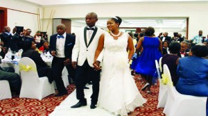 • PRESIDENT Michael Sata's son, Kazimu walks hand in hand with his wife Tiwonge Mukobeko during their wedding reception in Lusaka last weekend. Picture by STEPHEN KAPAMBWE