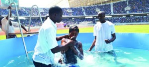 • ABOUT 1,000 witnesses were baptised yesterday at this year's convention of the Jehovah's Witnesses held at Levy Mwanawasa Stadium in Ndola. Above, a brother baptises a female baptism candidate.Picture By CHATULA KAMPO