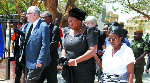 •ACTING President Dr Guy Scott  (left) with First Lady Dr Christine Kaseba (in black) during a wreath laying ceremony at President Sata's grave at Embassy Park yesterday. Picture by THOMAS NSAMA