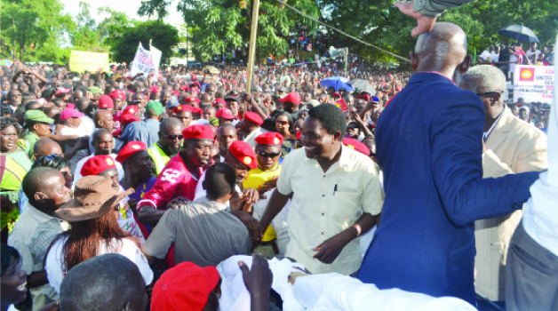 • UNITED Party for National Development president Hakainde Hichilema (smiling in the middle) being mobbed by supporters when he arrived for a rally at the Freedom Park in Kitwe yesterday. Picture by MOFFAT CHAZINGWA