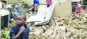 • A BOY stands near what used to be his home in Mazabuka which collapsed due to heavy rains on Wednesday.  Picture by EUGENE MUNYAMA