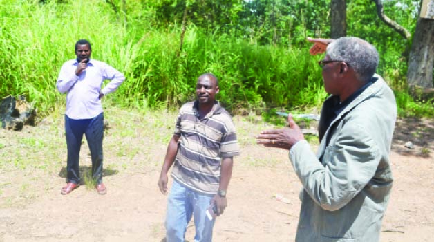 • NDOLA District Commissioner (DC) Rebby Chanda (right) shows Sunday Times staffers (not in picture) the land that will be de-gazetted for allocation to residents at Ndola Forest, while estate agent Felix Zimba looks on.  Picture by MUNAMBEZA MUWANEI