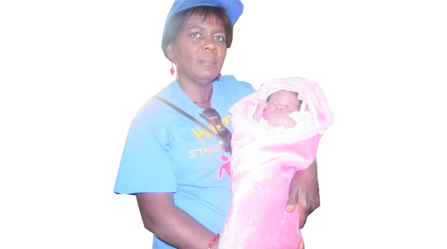 • MWEWOKANI Women's Organisation chairperson Charity Kalebaika holds baby Joy in the maternity wing at Nchanga North General Hospital in Chingola.