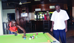 •KAFUBU Dam where the Ndola boating club is situated. (Inset) Boating club senior man, Milner Simukonda (standing)  and a patron Mwewa Chanda playing pool in the club lounge. Pictures by YVONNE CHATE.