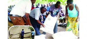 • DISASTER Management and Mitigation Unit officials (left) distribute mealie-meal to displaced families in Nkandabwe area in Sinazongwe following a tremor on New Year's Day. (Inset) Tents being mounted for the displaced families. Picture by CHILA NAMAIKO
