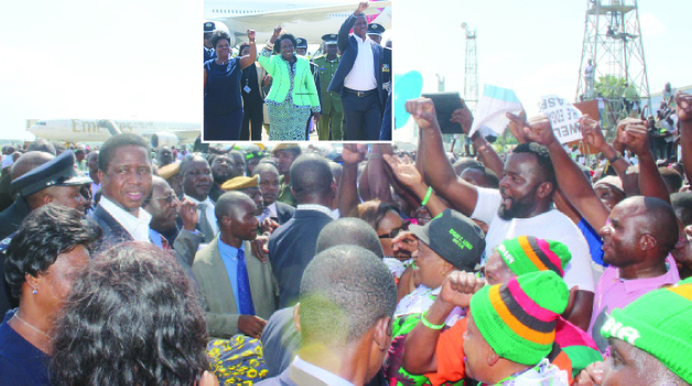 •A HEROES WELCOME: PRESIDENT Edgar Lungu and First Lady Esther being mobbed by a horde of jubilant supporters at the Kenneth Kaunda International Airport in Lusaka upon their arrival from France yesterday. (Inset) Mr Lungu, Vice-President , Inonge Wina and Ms Lungu flash the PF symbol. Picture by JEAN MANDELA