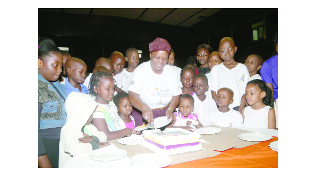 • FIRST Lady Esther Lungu shares in cutting the cake with children living with cancer during the commemoration of International Childhood Cancer Day at Mulungushi Conference Centre yesterday. Picture by ROYD SIBAJENE/ZANIS