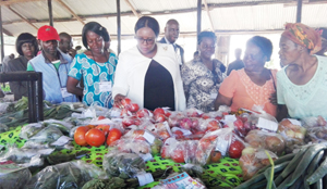 FARMERS also had fair shares of the annual exhibition: Agriculture Minister Dora Siliya (in white top) admires tomatoes when she visited stands at the Small scale farmers pavillion at the just ended CAMINEX. Picture by CHATULA KANGALI