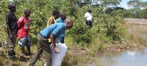 •RESIDENTS feeding Fish in Mukochi Dam as area MP Charles Zulu looks on.