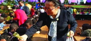 •A Zambia Chinese Association member hands over donated foodstuff to Open Arms Community School pupils recently.