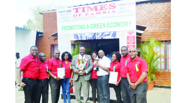 • THE WINNING TEAM...... Times Printpak employees with company managing director Beston Ng'onga (in suit) pose for a photo with two trophies after emerging best commercial exhibit and best media exhibit winners at the just-ended 91st Agriculture and Commercial Show of Zambia in Lusaka yesterday . Picture By JAJAH COULIBALY .