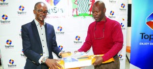 •TOPSTAR director sales Cliff Sichone(left) handing over a decoder to Francis Maingaila,first customer to buy a TopStar decoder reduced from K199 to K99 during the Press briefing at the TopStar head office in Lusaka yesterday. Picture by ROYD SIBAJENE/ZANIS