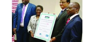 • INDO Zambia Bank (IZB) board chairperson Orlean Moyo (left) and IZB managing director Maheshkumar Bansal displays the credit rating certificate as IZB general manager Godwin Ngoma (far left) and Credit Rating Agency chairperson Wilson Kalumba (far right) look on. Picture by CASSEY KAYULA